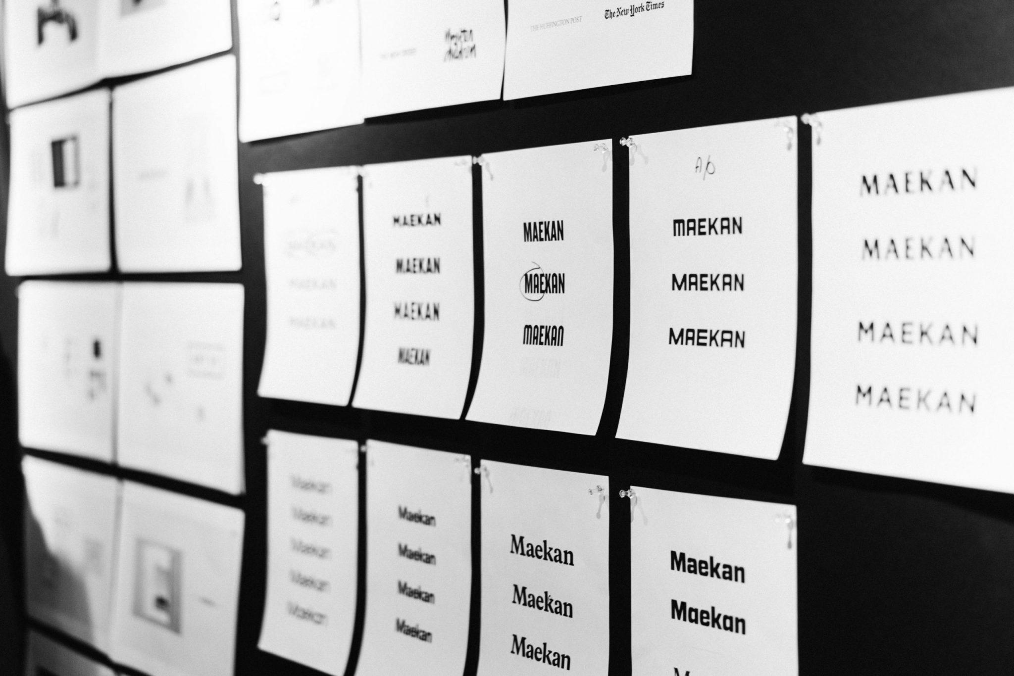A physical mood board of initial MAEKAN wordmark options