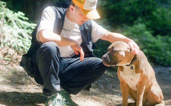 Kevin Wong wearing the Bricks & Wood x New Balance 57/40 and a Bricks & Wood eTc Tacoma t-shirt standing next to his dog Chibi.