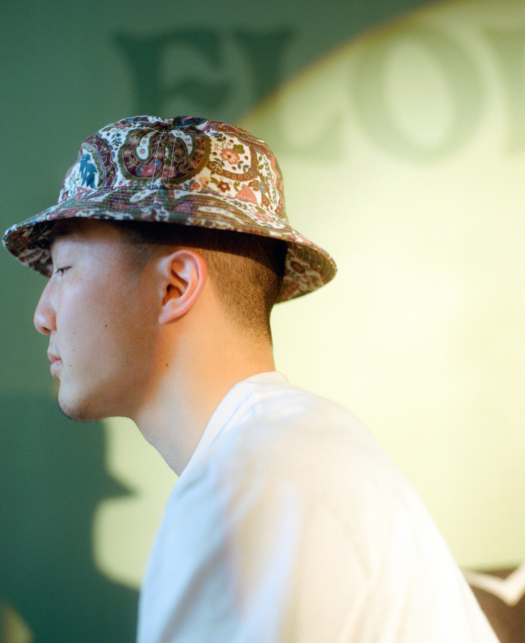 Kevin Wong wearing a bucket hat in front of a green painted wall in his lofted workspace in Oakland, California