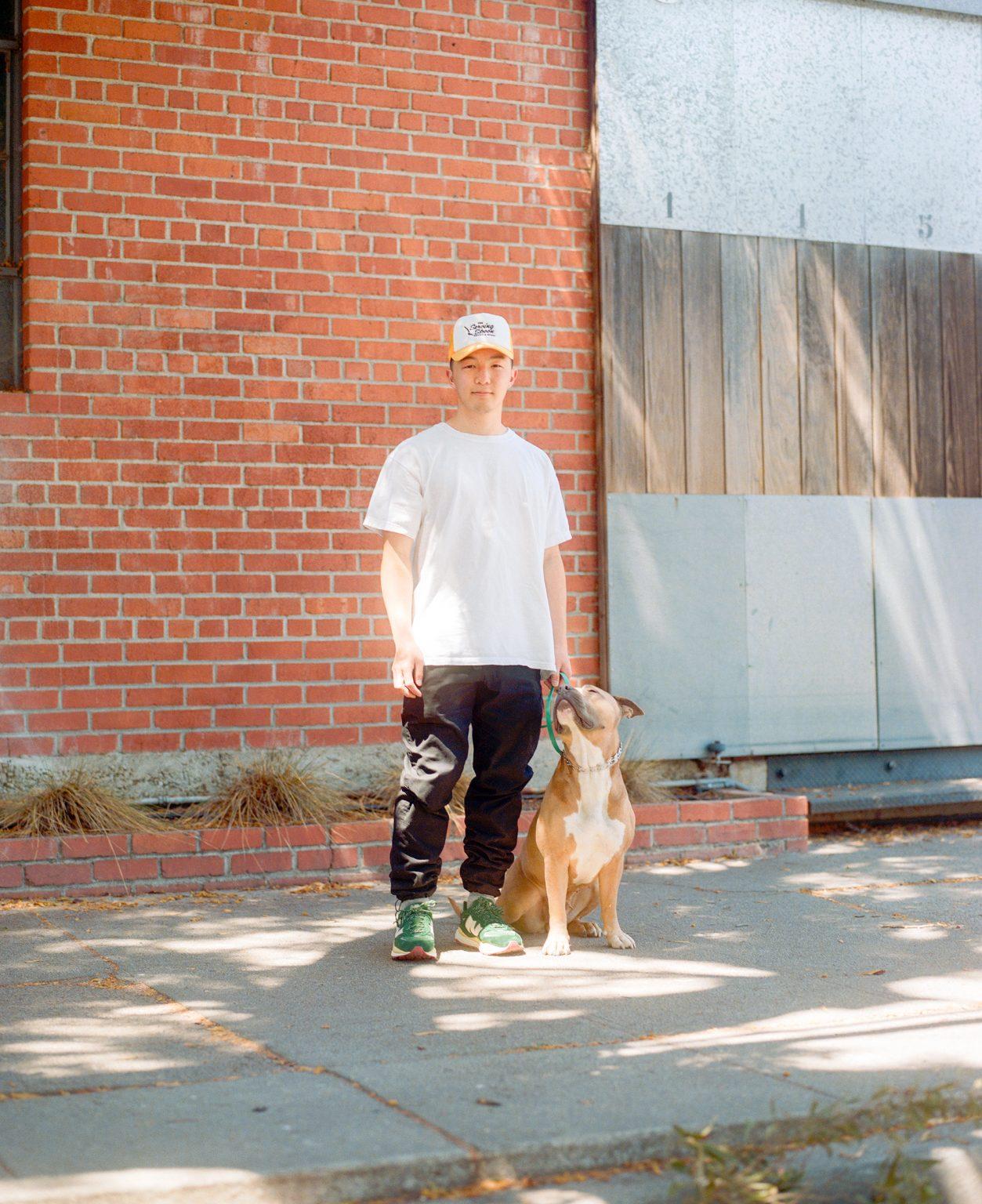 Kevin Wong standing next to his dog Chibi on a sun dappled sidewalk